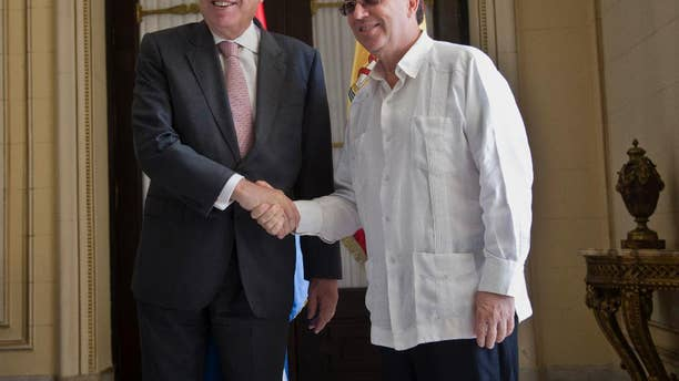 Cuba's Foreign Minister Bruno Rodriguez, right, and Spanish Foreign Minister Jose Manuel Garcia-Margallo pose for a photo prior to their meeting at the Foreign Ministry in Havana, Cuba, Tuesday, Nov. 25, 2014. Margallo is in Cuba on a three-day visit. (AP Photo/Ramon Espinosa)