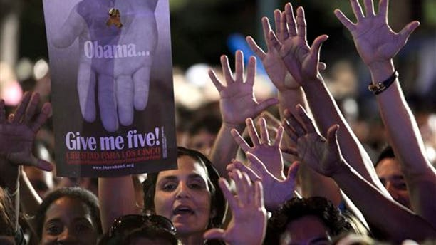 """A woman holds a poster that reads """"Obama give me five"""" during a concert in honor of the five intelligence agents in Havana, Cuba, Saturday, March 1, 2014. Thousands of Cubans rallied at the University of Havana on Saturday night for a concert to give a hero's welcome to the second of five intelligence agents to return to the island after completing long prison terms in the United States. (AP Photo/Franklin Reyes)"""