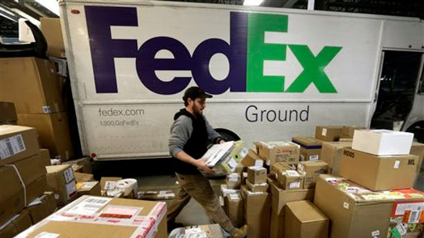FILE - In this Dec. 16, 2013 file photo, package handler Chris Addison arranges packages before loading a delivery truck at a FedEx sorting facility in Kansas City, Mo. Santa's sleigh didn't make it in time for Christmas for some this year due to shipping problems at UPS and FedEx.The delays were blamed on poor weather earlier this week in parts of the country as well as overloaded systems.  (AP Photo/Charlie Riedel)