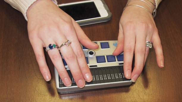 In this Wednesday, March 26, 2014 photo, Megan Dausch, an instructor at the Helen Keller National Center, demonstrates the use of a Braille reader that helps blind clients access the Internet, in Sands Point, N.Y. The center, based in suburban New York, is leading an effort to distribute $10 million annually in high-technology equipment to assist low-income deaf and blind consumers across the country. (AP Photo/Frank Eltman)