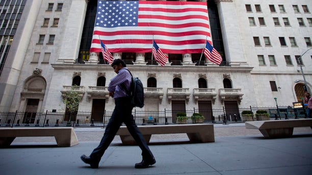 File: In this Aug. 5, 2011, photo a pedestrian walks past the New York Stock Exchange in New York.