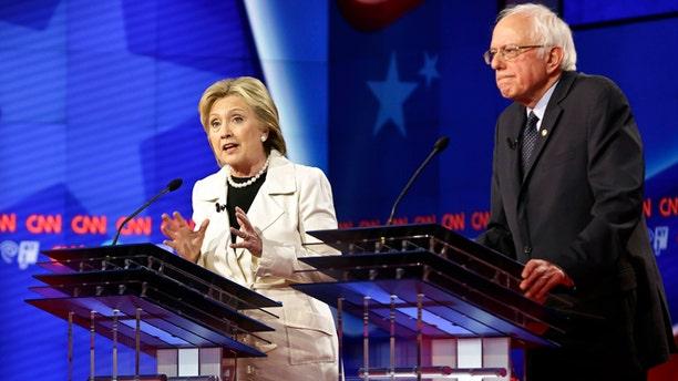 Democratic presidential candidates Sen. Bernie Sanders, I-Vt., right, listens as Hillary Clinton speaks during the CNN Democratic Presidential Primary Debate at the Brooklyn Navy Yard Thursday, April 14, 2016, New York. (AP Photo/Seth Wenig)