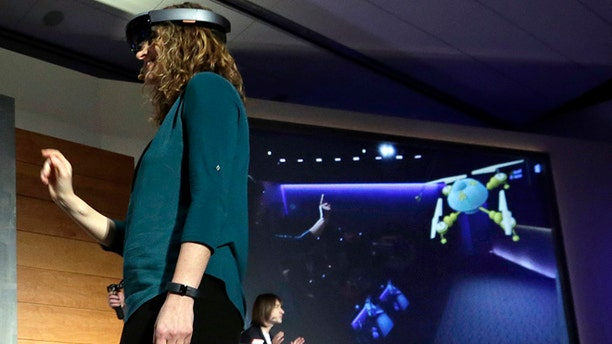 """In this photo taken Wednesday, Jan. 21, 2015, Microsoft's Lorraine Bardeen demonstrates a hologram device as what she """"sees"""" is projected on a screen behind during an event at the company's headquarters in Redmond, Wash. With the new HoloLens headset, Microsoft is offering real-world examples to show how you might use three-dimensional digital images _ or holograms _ in daily life. (AP Photo/Elaine Thompson)"""