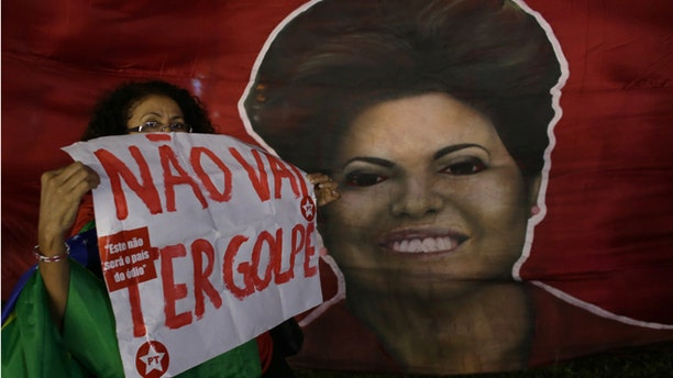 """Woman shows poster written in Portuguese """"There will not be a coup"""" next to a picture of Brazil's President Dilma Rousseff, during a rally in her support and of former President Luiz Inacio Lula da Silva, in Brasilia, Brazil, Friday, March 18, 2016. Supporters of Silva and Rousseff gathered for rallies in a handful of cities across Brazil, particularly in the industrial south, where the former factory worker has his base. Silva has been tied to a sprawling corruption investigation involving the Brazil oil giant Petrobras. (AP Photo/Eraldo Peres)"""