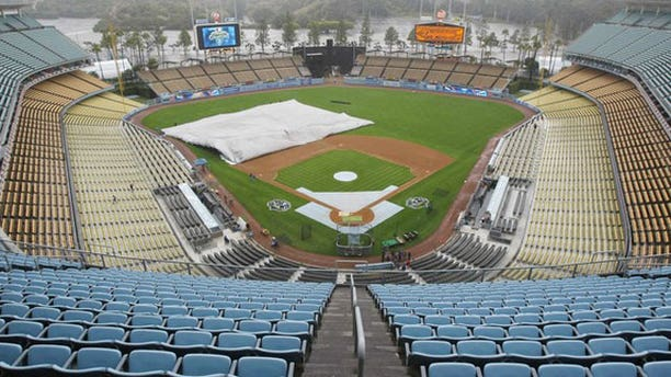 October 4, 2009: Grounds crew remove a rain protecting tarp from the field at Dodger Stadium before the Los Angeles Dodgers and the Philadelphia Phillies take batting practice in preparation for their MLB National League Championship playoff baseball series in Los Angeles.