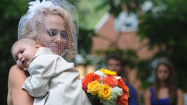 Aug 3, 2013: Christine Swidorsky carries her son and the couple's best man, Logan Stevenson, 2, down the aisle to her husband-to-be Sean Stevenson during the wedding ceremony in Jeannette, Pa.