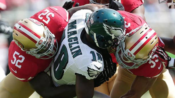 Philadelphia Eagles wide receiver Jeremy Maclin (18) is tackled by San Francisco 49ers linebacker Patrick Willis (52) and safety Eric Reid (35) during the first quarter of an NFL football game in Santa Clara, Calif., Sunday, Sept. 28, 2014. (AP Photo/Marcio Jose Sanchez)