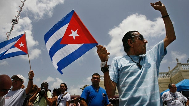 """MIAMI - AUGUST 1:  Angel Febles (R) of Miami Beach, Florida, waves a Cuban flag and shouts """"Viva Cuba libre"""" in front of Versallies Restaurant in the Little Havana neighborhood August 1, 2006 in Miami, Florida. Febles immigrated to the U.S. from Cuba in 1960. Cuban Americans were celebrating the news that Fidel Castro had turned over power to his younger brother, Raul Castro, while he undergoes medical treatment for intestinal bleeding.  (Photo by Chip Somodevilla/Getty Images)"""