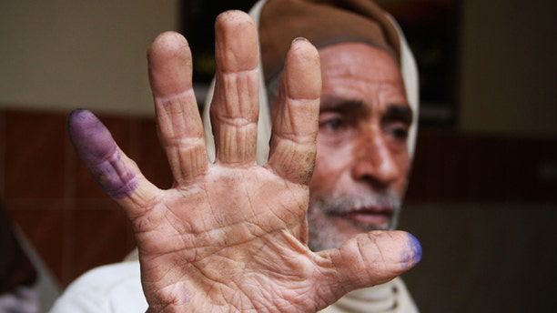 Dec. 14: An Egyptian man shows his inked fingers after casting his vote in Menoufia, Egypt.