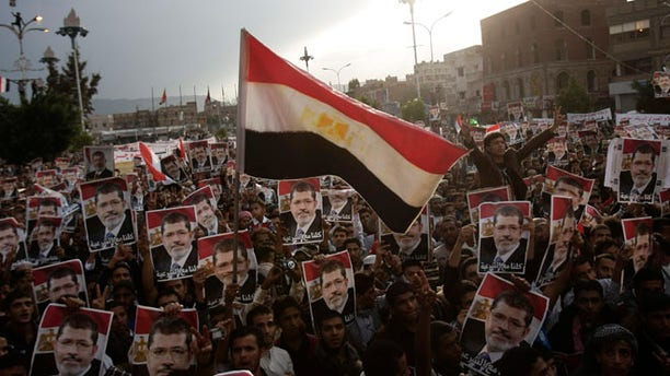 Aug 15, 2013: Yemeni protesters wave an Egyptian flag as they hold posters of Egypt's ousted President Mohammed Morsi during a rally supporting Morsi in Sanaa, Yemen.