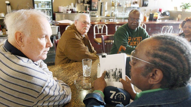 FILE - In this Jan. 23, 2009, file photo, Elwin Wilson, left, and Friendship 9 member Willie McCleod, right, look over pictures from civil rights incidents in Rock Hill, S.C., in the 1960s. The criminal record will soon be erased for the nine black men arrested for integrating a whites-only South Carolina lunch counter 54 years ago. On Wednesday, Jan. 28, 2015,  prosecutor is expected to ask a judge to vacate the arrests and convictions of the men known as the Friendship 9. (AP Photo/Herald, Andy Burriss, File)