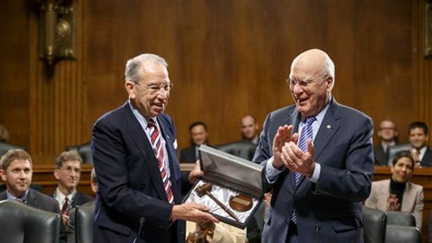 Sen. Patrick Leahy, D-Vt., center, the outgoing chairman of the Senate Judiciary Committee, applauds new committee chairman Sen. Chuck Grassley, R-Iowa, left, on Capitol Hill in Washington, Thursday, Jan. 22, 2015, after presenting Grassley a new gavel as the veteran senators hold an organizational meeting under the new Republican majority. (AP Photo/J. Scott Applewhite)