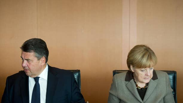 German Chancellor Angela Merkel, right, and Vice Chancellor and Economic Minister Sigmar Gabriel arrive for the weekly cabinet meeting in the Federal Chancellery in Berlin, Wednesday, Oct. 29, 2014. (AP Photo/Steffi Loos)