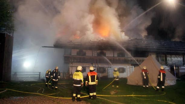 Firefighters try to extinguish a fire  in the Bavarian town of Schneizlreuth , Germany, early Saturday May 23, 2015. Police in Germany say six people are missing after a fire at a guesthouse in Bavaria. In a statement Saturday, police said the fire broke out overnight in a converted farmhouse in the town of Schneizlreuth, southeast of Munich near the border with Austria. Of the 47 people staying at the guesthouse, 41 were able to flee.   ( Ferdinand Farthofer/aktivnews/dpa  via AP)