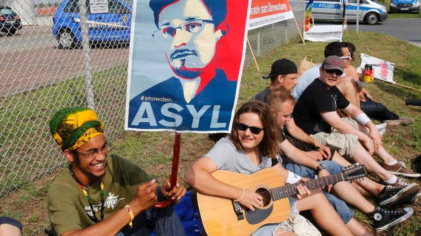 A demonstrator against spying holds a sign asking for asylum for former NSA contractor Edward Snowden outside US Army's 'Dagger Complex' near Griesheim, Germany, Saturday, July 26, 2014. The massively secured property is run by the US Military and supposed to be used by the US intelligence agency NSA (National Security Agency).  (AP Photo/Michael Probst)(AP Photo/Michael Probst)