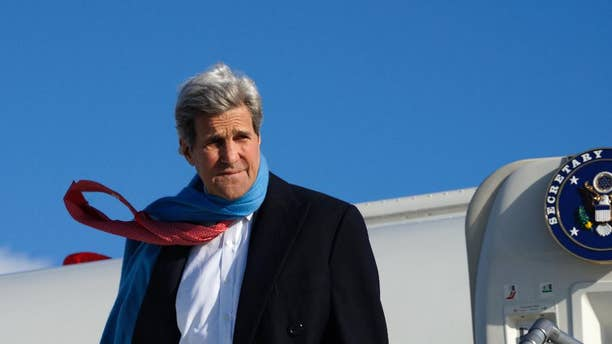 U.S. Secretary of State John Kerry reacts to the blustery weather on arrival in Munich, Germany on Saturday Jan. 10, 2015.  Kerry was to meet Sultan Qaboos of Oman in Munich before traveling on to India.  (AP Photo/Rick Wilking. Pool)