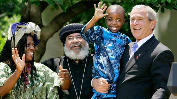 "In this May 30, 2007, file photo President Bush, right, hoists 4-year-old Baron Mosima Loyiso Tantoh, son of Manyongo Mosima ""Kuene"" Tantoh of South Africa, left, who is HIV-positive, after speaking about his efforts to fight HIV/AIDS worldwide, in the Rose Garden of the White House in Washington. (AP Photo/J. Scott Applewhite, File)"