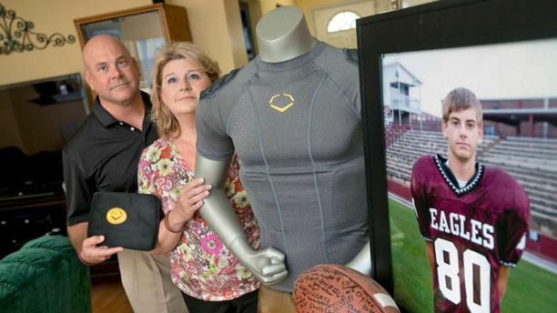 Brian and Kathy Haugen stand near a photo of their son, Taylor Haugen. The Haugens have donated nearly 800 EvoShield HYBRIDPRO Protective Rib shirts (shown here) to young athletes since Taylor's death.
