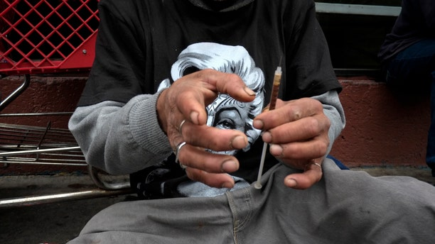 A drug addict prepares a needle to inject himself with heroin in front of a church in the Skid Row area of Los Angeles. (AP Photo/Jae C. Hong)