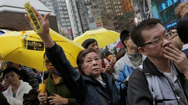 December 15, 2014: A protester raises a yellow banner that reads 'I want genuine universal suffrage' while police clear barricades and tents on a main road in the occupied areas at Causeway Bay district in Hong Kong. (AP Photo/Vincent Yu)