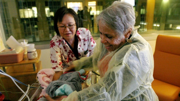 Hospital volunteer Gertie Rogers, 84, places a newborn baby back into a bed in the neonatal intensive care unit at the University of Chicago's Comer Children's Hospital in Chicago. (AP Photo/Martha Irvine)