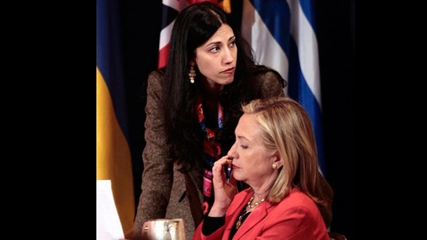 In this Sept. 20, 2011 file photo, Huma Abedin, top, deputy chief of staff and aide to Secretary of State Hillary Rodham Clinton, right, during a meeting with leaders for the Open Government Partnership in New York.