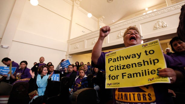 FILE: January 29, 2013: Ana Castro, a union member, chants after President Obama's speech on immigration, inside La Plaza United Methodist Church in Los Angeles, Calif.