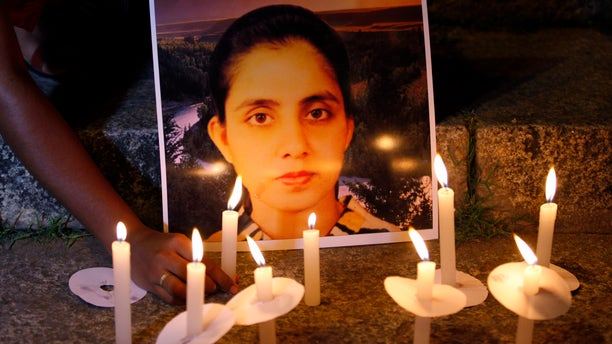 Dec. 13, 2012 - A student of a nursing college places a candle in front of a picture depicting nurse Jacintha Saldanha, during a candle-lit vigil  in Bangalore, India.