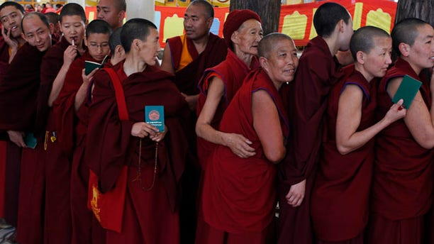 March 20, 2011: Exile Tibetan Buddhist monks and nuns line up with their green books to cast their votes during the final round of voting to choose the next exile Tibetan prime minister and the members of the Tibetan parliament-in-exile in Dharmsala, India.