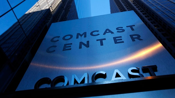A sign outside the Comcast Center, left, is shown in Philadelphia.