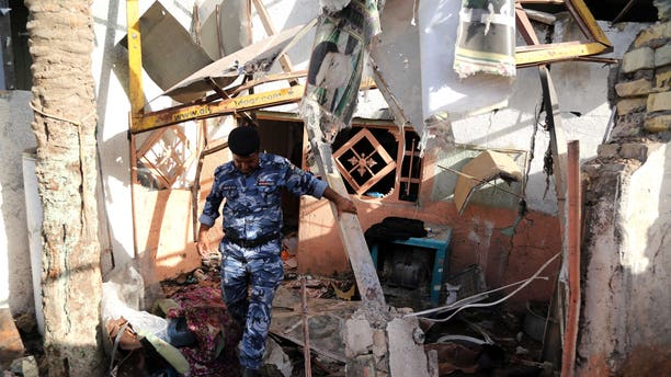 Sept. 19, 2014 - An Iraqi federal policeman inspects the site of the aftermath of a car bomb attack the northern Shiite district of Kazimiyah, in Baghdad, Iraq. A series of bomb & mortar shell attacks in and around Baghdad killed 20, Iraqi officials said.