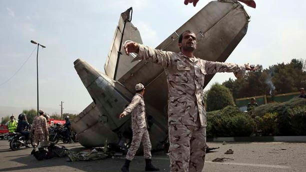 Aug. 10, 2014: Iranian Revolutionary Guards prevent the media from approaching the wreckage of a passenger plane crash near the capital Tehran, Iran. (AP)