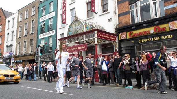 June 6, 2012: Irish boxer Kenny Egan, 30, carries the Olympic torch past the Olympia Theater as he runs through central Dublin, Ireland.