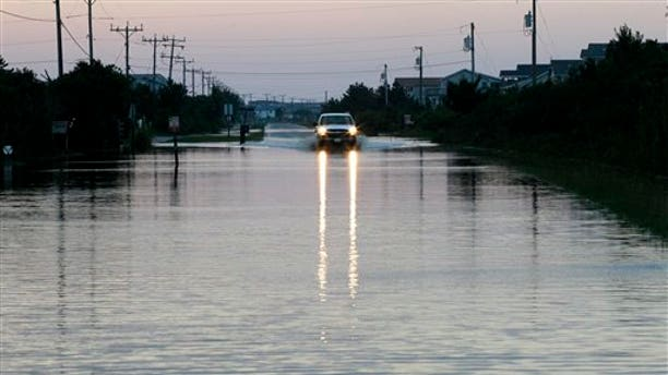 Aug. 28: A vehicle navigates through water in the road left behind by Hurricane Irene in Nags Head, N.C. The hurricane unloaded more than a foot of water on North Carolina, spun off tornadoes in Virginia, Maryland and Delaware, and left 3 million homes and businesses without power as it moved up the East Coast.