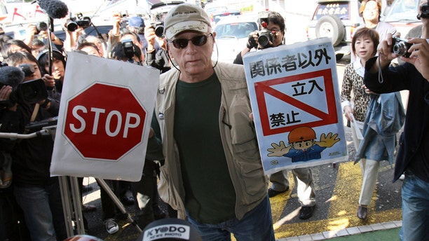 """In this Nov. 2, 2010, file photo, Ric O'Barry, a leading global dolphin activist whose efforts to save dolphins is documented in the Oscar-winning film """"The Cove,"""" holds """"Stop"""" and """"Keep out except persons concerned"""" signs as he arrives at Taiji Community Center in Taiji, western Japan."""