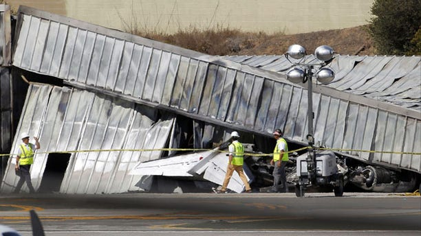 September 30, 2013: Investigators stand near a hangar at the site of a plane crash in Santa Monica, Calif. Monday. (AP Photo)