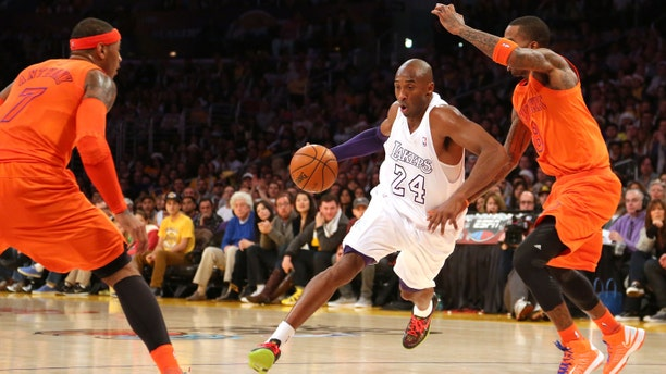 Kobe Bryant #24 of the Los Angeles Lakers dribbles to the basket against J.R. Smith #8 and Carmelo Anthony #7 of the New York Knicks in the first half during the NBA game at Staples Center on December 25, 2012 in Los Angeles, California.(Photo by Victor Decolongon/Getty Images)