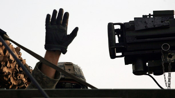 Aug. 18, 2010: A U.S. Army soldier from 2nd Battalion, 23rd Infantry Regiment, 4th Brigade, 2nd Infantry Division waves from his Stryker armored vehicle after crossing the border from Iraq into Kuwait.