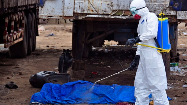 August 12, 2014: The body of a man found in the street, suspected of dying from the ebola virus is sprayed with disinfectant, in the capital city of Monrovia, Liberia.  (AP Photo/Abbas Dulleh)