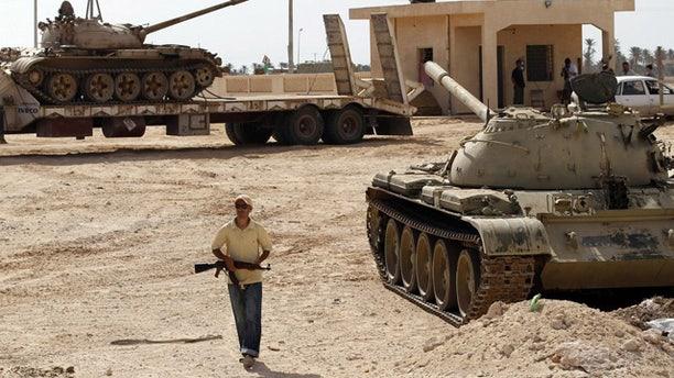 Aug 29: A rebel fighter walks between T-55 tanks in Misrata.