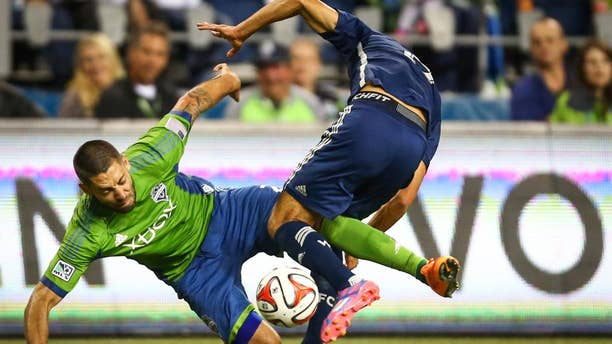 Seattle Sounders player Clint Dempsey tangles with a Vancouver Whitecaps player in the second half on Friday, October 10, 2014. The Whitecaps won the Cascadia Cup after beating the Sounders 1-0. (AP Photo/seattlepi.com, Joshua Trujillo)