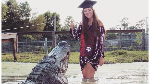 """Makenzie Noland, 21, poses with a gator named """"Big Tex"""" at Gator Country in Beaumont, Texas, on August 3, 2018."""