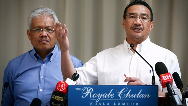 April 19, 2014: Malaysian Deputy Minister of Foreign Affairs Hamzah Zainudin, left, listens as Malaysia's acting Transport Minister Hishammuddin Hussein answers a question from a journalist during a press conference on the missing Malaysia Airlines Flight 370 at a hotel in Kuala Lumpur. (AP Photo/Vincent Thian)
