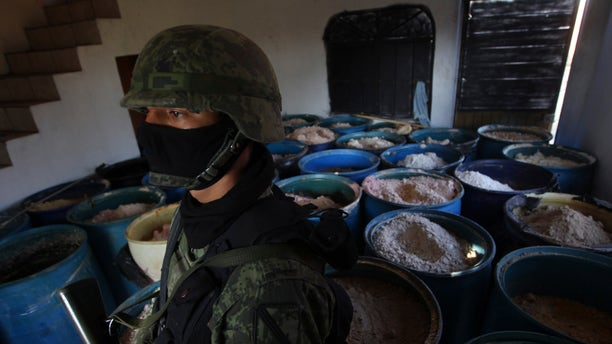 Soldier stands in a room full of barrels containing white and yellow powder after a seizure of 15 tons of pure methamphetamine at a small ranch in Tlajomulco de Zuniga,