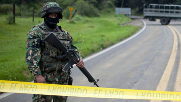 A Navy Marine stands behind tape marking the perimeter around an armored U.S. Embassy vehicle, not in the picture, after it was attacked by unknown assailants on the highway leading to the city of Cuernavaca, near Tres Marias, Mexico, Friday, Aug. 24, 2012. Two U.S. government employees were shot and wounded in an attack on their vehicle south of Mexico City on Friday, a law enforcement official said. (AP Photo/Alexandre Meneghini)