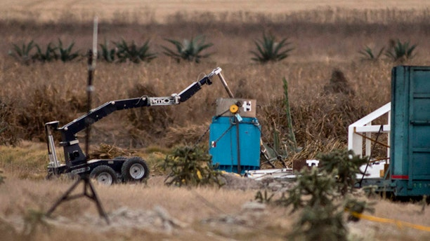 A robotic arm recovers radioactive cobalt-60 and deposits it in a safe container on a field in the town of Hueypoxtla, central Mexico, Tuesday Dec. 10, 2013.
