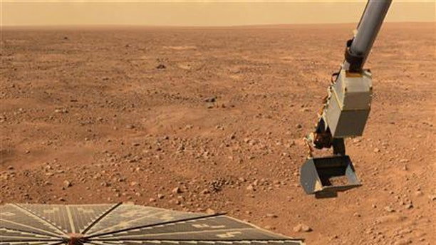 NASA's Phoenix Mars Landers solar panel and the lander's Robotic Arm with a sample in the scoop are seen in this image taken June 10, 2008, by the lander's Surface Stereo Imager.