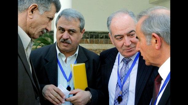 March 24, 2013: Syrian Alawites Mahmoud Maraie, second left, and Bassam al-Malek, second right, talk with other members of the Syrian Alawite sect who are opposed to Syrian President Bashar Assad in Cairo, Egypt. Members of Assad's Alawite sect met in Cairo on Sunday in an attempt to distance themselves from the Damascus regime in its crack down on the Syrian revolution.