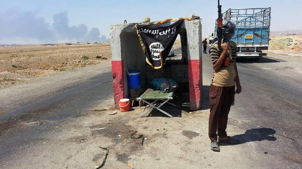 FILE - In this file photo taken Thursday, June 19, 2014, an al-Qaida-inspired militant stands guard at a checkpoint captured from the Iraqi Army outside Beiji refinery, some 250 kilometers (155 miles) north of Baghdad, Iraq. As Islamic militants rampaged across northern Iraq in June, seizing vast swaths of territory and driving hundreds of thousands of people from their homes, the Shiite Turkmens living in the hardscrabble town of Amirli decided to stay and fight. (AP Photo, File)