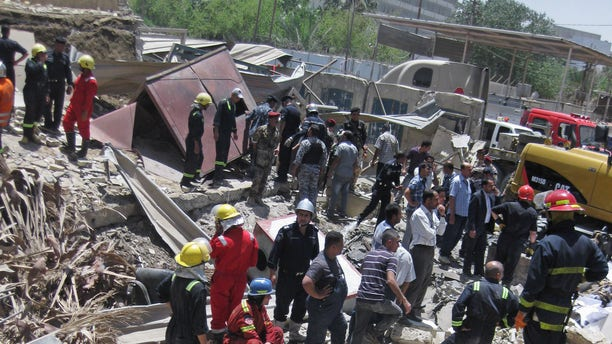 Firefighters and rescuers search for victims at the site of a bomb attack in the central Bab al-Muadham area in Baghdad, Iraq, Monday, June 4, 2012. A suicide bomber detonated explosives in a car outside Iraq's main religious affairs office for Shiite Muslims tearing down part of the three-story building and killed and wounded scores of people, police said. (AP Photo/Hadi Mizban)